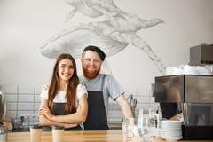 Concepto del negocio del café - el hombre barbudo joven positivo y los pares atractivos hermosos del barista de la señora gozan e imagen de archivo