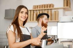 Concepto del negocio del café - retrato del barista de la señora en el delantal que prepara y que cuece la leche al vapor para la Foto de archivo libre de regalías