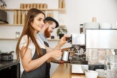 Concepto del negocio del café - retrato del barista de la señora en el delantal que prepara y que cuece la leche al vapor para la Fotografía de archivo