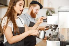 Concepto del negocio del café - retrato del barista de la señora en el delantal que prepara y que cuece la leche al vapor para la Imagenes de archivo