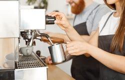 Concepto del negocio del café - retrato del barista de la señora en el delantal que prepara y que cuece la leche al vapor para la Fotos de archivo