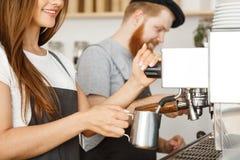 Concepto del negocio del café - retrato del barista de la señora en el delantal que prepara y que cuece la leche al vapor para la Fotos de archivo libres de regalías