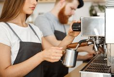 Concepto del negocio del café - retrato del barista de la señora en el delantal que prepara y que cuece la leche al vapor para la Imagen de archivo libre de regalías