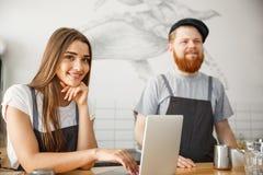 Concepto del negocio del café - retrato de los pequeños socios comerciales que trabajan junto en su cafetería fotos de archivo