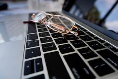 Concepto del negocio, cierre para arriba, vidrios en el ordenador portátil foto de archivo