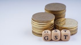 Concepto del negocio con una palabra de GST en monedas apiladas Fotografía de archivo libre de regalías