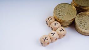 Concepto del negocio con una palabra de GST en monedas apiladas foto de archivo