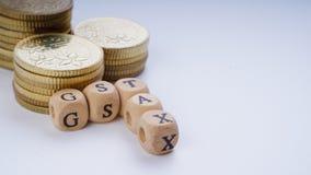 Concepto del negocio con una palabra de GST en monedas apiladas Fotos de archivo