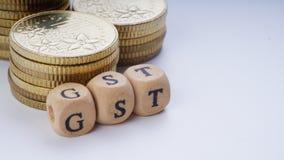 Concepto del negocio con una palabra de GST en monedas apiladas Foto de archivo libre de regalías