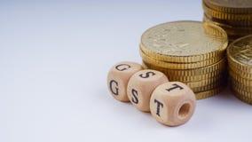 Concepto del negocio con una palabra de GST en monedas apiladas Imágenes de archivo libres de regalías
