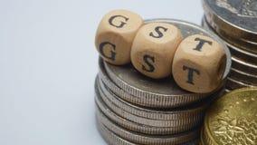 Concepto del negocio con una palabra de GST en monedas apiladas Fotografía de archivo