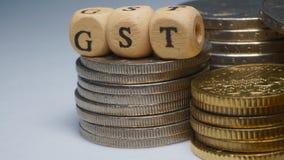 Concepto del negocio con una palabra de GST en monedas apiladas Imagen de archivo libre de regalías