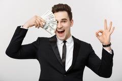 Concepto del negocio: El hombre de negocios joven confiado que sostiene el dinero y que muestra muy bien firma encima el fondo gr Imagenes de archivo