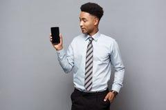 Concepto del negocio - hombre de negocios afroamericano profesional hermoso feliz que muestra el teléfono móvil al cliente Foto de archivo