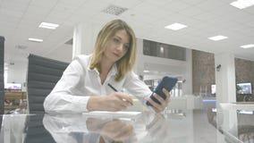 Concepto del negocio: la mujer de negocios toma notas del teléfono metrajes
