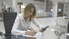Concepto del negocio: la mujer de negocios toma notas del teléfono almacen de video