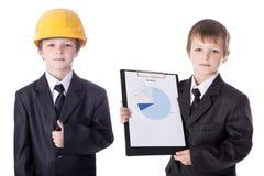 Concepto del negocio y de la construcción - niños pequeños en traje de negocios Imagen de archivo