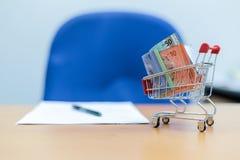 Concepto del negocio y de las finanzas Notas del ringgit malasio sobre la tabla con el papel y la pluma silla azul borrosa imágenes de archivo libres de regalías