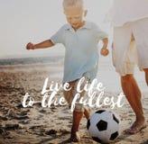 Concepto del niño de la playa del balón de fútbol de Live Life To The Fullest Fotografía de archivo