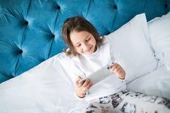 Concepto del niño, de la tecnología y de Internet - niña que miente en cama con el smartphone que juega a juegos en casa Imagen de archivo