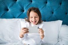 Concepto del niño, de la tecnología y de Internet - niña que miente en cama con el smartphone que juega a juegos en casa Fotos de archivo