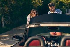 Concepto del ocio, del viaje por carretera, del viaje y de la gente - amigos felices que empujan el coche roto del cabriolé a lo  imagen de archivo