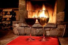 Concepto del partido del vino del lugar de la chimenea Dos vidrios de vino blanco rojo, fondo de la chimenea postal romántica de  imagen de archivo libre de regalías