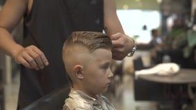 Concepto del peinado del muchacho Peluquero que hace hairstyling de los niños en peluquería de caballeros Peluquero que crea el p almacen de video