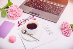 Concepto del planeamiento del día Taza de café en el cuaderno con para hacer la lista, el ordenador portátil, el sketchbook, los  Imagen de archivo libre de regalías
