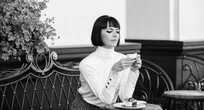 Concepto del postre Tiempo y relajación agradables Bocado delicioso y gastrónomo La muchacha relaja el café con café y el postre fotos de archivo libres de regalías