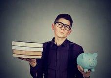 Concepto del préstamo del estudiante Hombre con la pila de hucha de los libros por completo de la deuda Fotografía de archivo