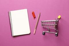 Concepto del presupuesto carro de la compra, cuaderno de papel en blanco foto de archivo