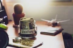 Concepto del presupuesto de las vacaciones Dinero para los ahorros de las vacaciones en un vidrio foto de archivo libre de regalías