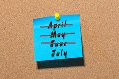 Concepto del principio de julio Etiqueta engomada con hacia fuera cruzados los meses abril, mayo y junio Mensaje en el corkboard  Fotos de archivo libres de regalías