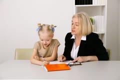 Concepto del profesor y del alumno Profesor particular que ayuda con la preparación a la niña imagenes de archivo
