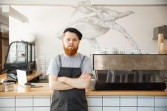 Concepto del propietario de negocio del café - retrato del barista caucásico barbudo joven feliz en delantal con la mirada confia fotografía de archivo