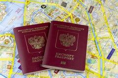 concepto del recorrido Dos pasaportes rusos en el fondo de un mapa de papel de la ciudad imagen de archivo