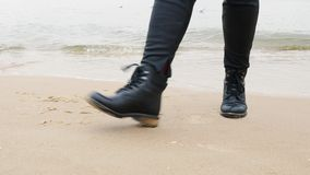 concepto del recorrido Los pies de las mujeres en los zapatos de cuero que bailan en la arena por el mar y el stopout en ondas metrajes