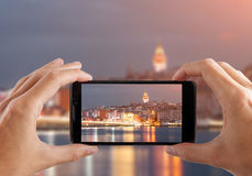 concepto del recorrido Manos que hacen la foto de ciudad de la noche con la cámara del smartphone Estambul en la puesta del sol T Fotografía de archivo libre de regalías