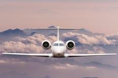 concepto del recorrido Vista delantera del avión de pasajeros del jet en vuelo con el fondo del cielo, de la nube y de la montaña Foto de archivo libre de regalías