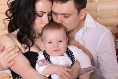 Concepto del ` s del Año Nuevo de la familia La mamá y el papá besan a su niño Imagen de archivo