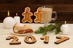 Concepto del `s del Año Nuevo Cena de la Navidad: pan de jengibre, rama spruce, capuchino con la empanada, velas Fotografía de archivo libre de regalías