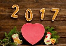 Concepto del `s del Año Nuevo Encajone las galletas en forma de corazón del pan de jengibre, la rama y el número 2017 del abeto Fotografía de archivo libre de regalías