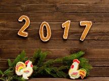 Concepto del `s del Año Nuevo Gallos del cuadro 2017 y dos del pan de jengibre, rama del abeto en un fondo de madera Foto de archivo
