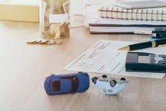 Concepto del seguro de coche: La forma de demanda del coche con desplome del juguete del coche en el escritorio y el dinero acuña imagen de archivo libre de regalías