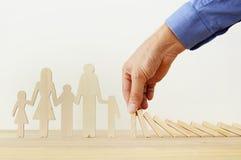 Concepto del seguro Hombre de negocios que protege a una familia contra efecto de dominó vida, financiero y problemas de salud foto de archivo libre de regalías