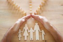 Concepto del seguro Hombre de negocios que protege a una familia contra efecto de dominó vida, financiero y problemas de salud fotografía de archivo libre de regalías