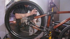 Concepto del servicio de la bicicleta Un hombre joven repara y mantiene una bicicleta en el taller metrajes