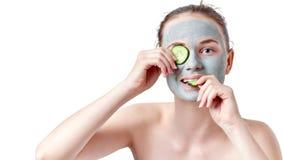 Concepto del skincare del adolescente Muchacha adolescente joven con la máscara facial de la arcilla seca que sostiene dos rebana Fotografía de archivo libre de regalías