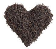 Concepto del té Hojas de té bajo la forma de corazón en un fondo blanco Fotografía de archivo libre de regalías